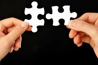 両手に持ったパズルのピース