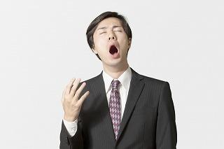 あくびするスーツ姿の男性