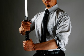 スーツを着て刀を抜いた男性