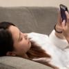 寝そべってスマートフォンを触る女性